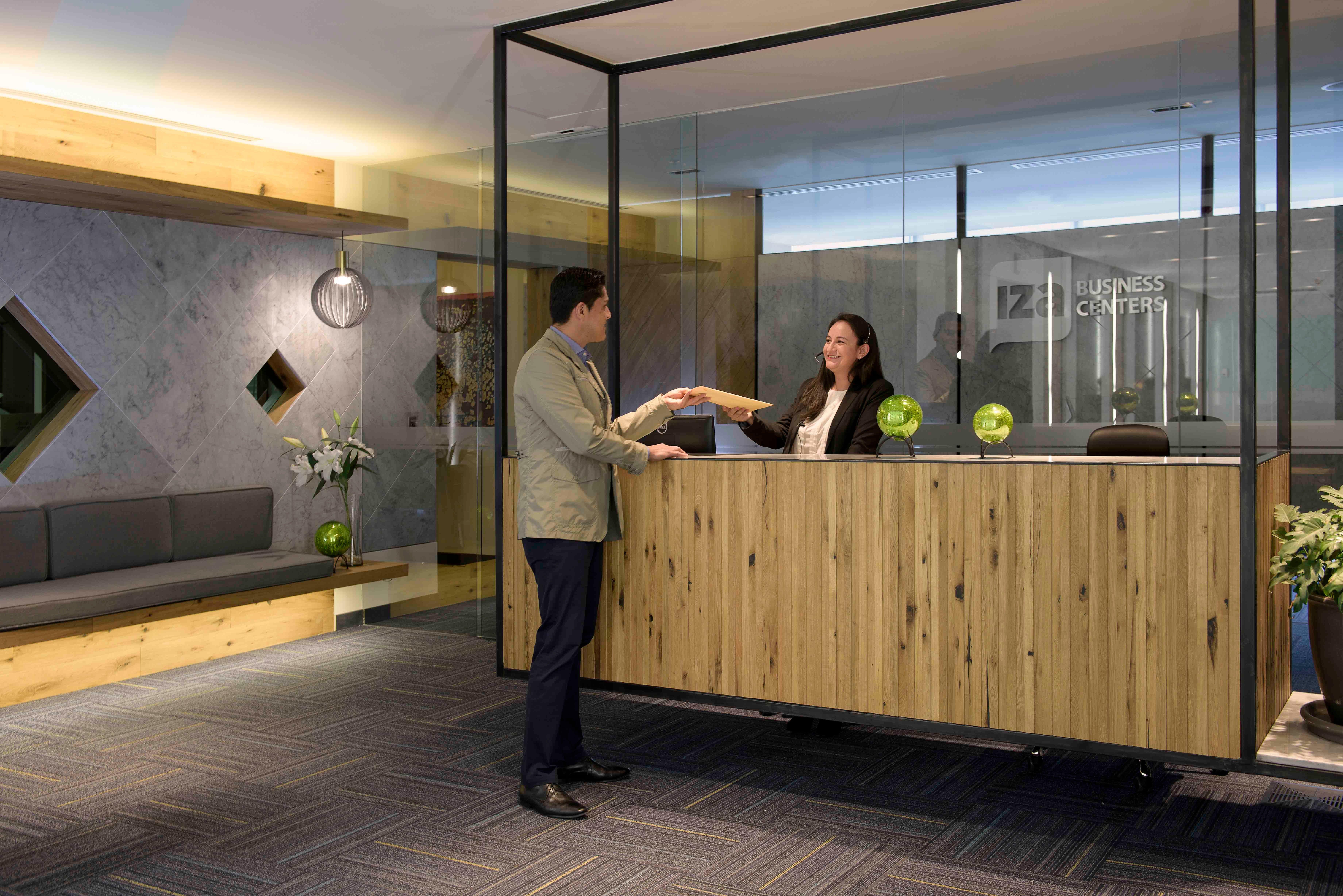 Recepcion IZA Business Centers atendiendo cliente oficina